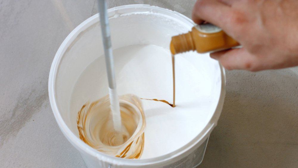 A man mixing interior paint with exterior paint