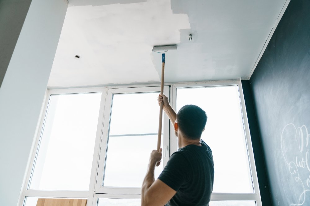 A man painting ceiling tiles