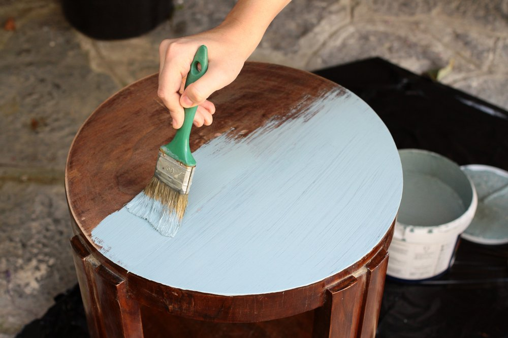 A women painting metal with chalk paint