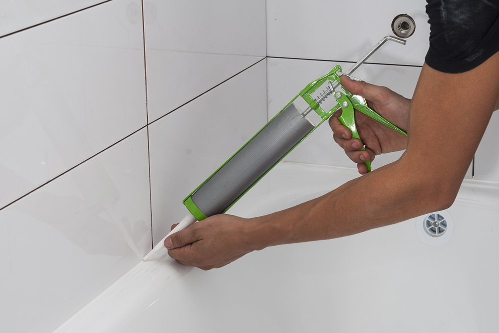 A man caulking over grout in a bathroom
