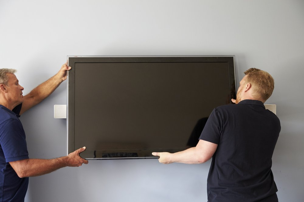 Two men mounting a TV on a wall without wall studs