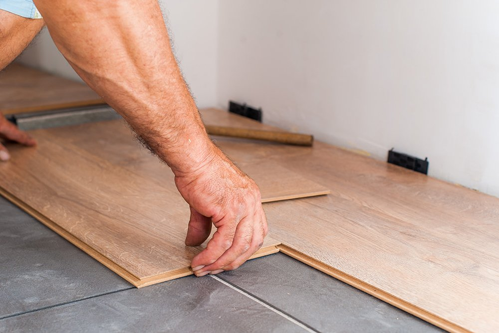A tradesman sealing laminate flooring